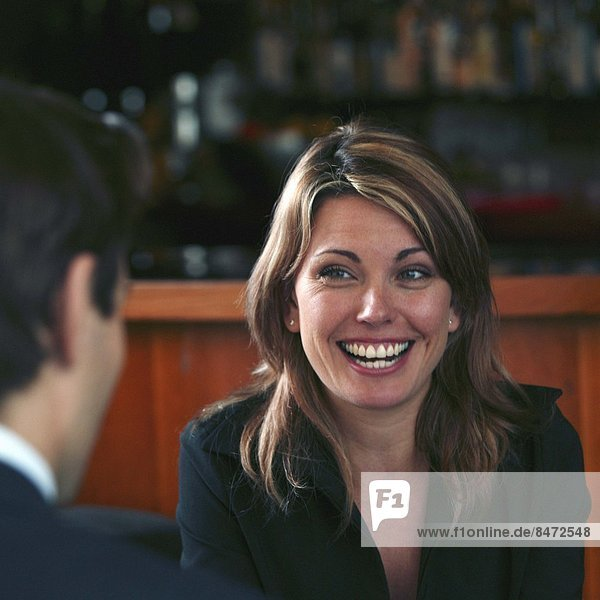 A woman talking to a businessman in a hotel bar  laughing