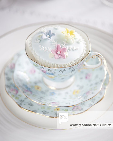 A floral china cup  saucer and plates  with iced cupcake