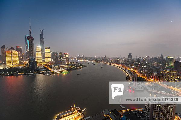 Skyline Finanzviertel mit Oriental Pearl Tower  Shanghai Tower  Pudong und Bund Promenade mit Fluss Huangpu in der Abenddämmerung  Shanghai  China