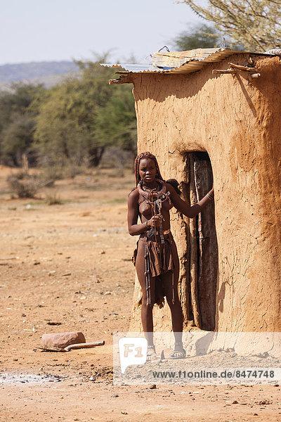 Junge Himba vor ihrer Hütte  traditioneller Schmuck für Mädchen im heiratsfähigen Alter  Kaokoland  Namibia