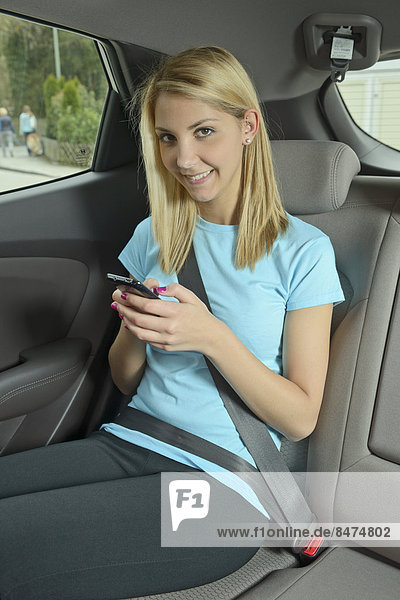 sitzend junge Frau junge Frauen Anschnallgurt Gurt Sitzmöbel Auto befestigen Sitzplatz