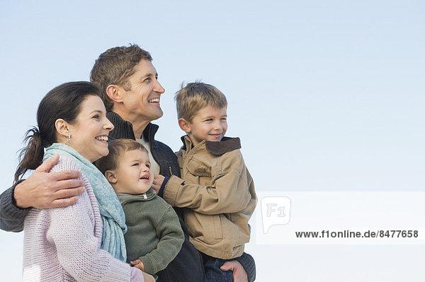 Parents with kids (12-17 months  6-7) under blue sky
