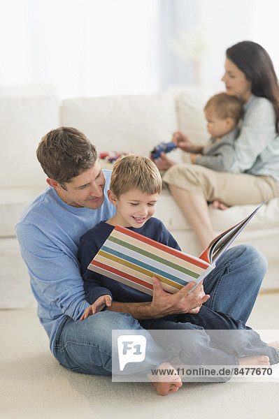 Parents with kids (12-17 months  6-7) at home  father reading to son
