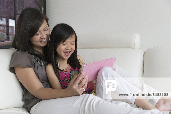 Asian mother and daughter using digital tablet on sofa