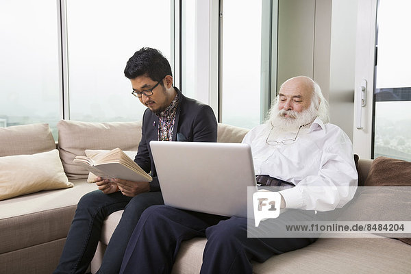 Grandfather using laptop while grandson reading book on sofa at home