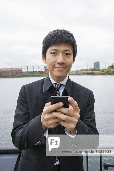 Außenaufnahme  Portrait  Geschäftsmann  Telefon  Text  Kurznachricht  Hoffnung  Handy  freie Natur