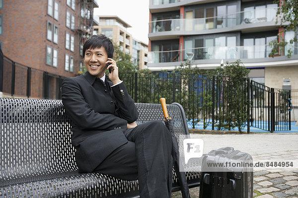benutzen  Fröhlichkeit  Geschäftsmann  Telefon  Gepäck  Sitzbank  Bank  Mittelpunkt  Handy  Erwachsener