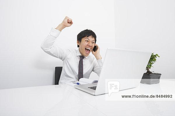 Schreibtisch  Geschäftsmann  jubeln  Telefon  Büro  Mittelpunkt  Handy  Erwachsener