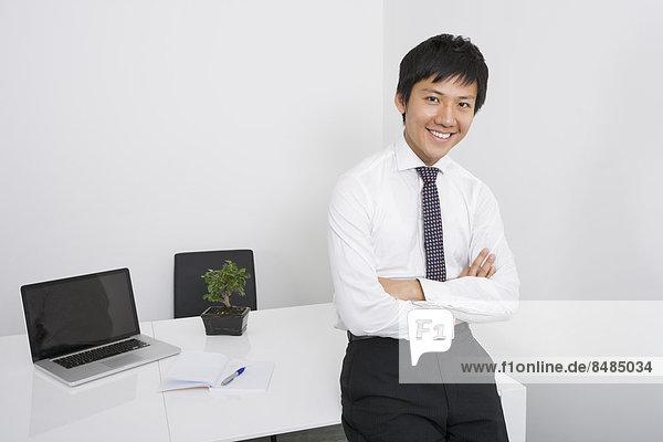 angelehnt  überqueren  Portrait  Schreibtisch  Fröhlichkeit  Geschäftsmann  Büro
