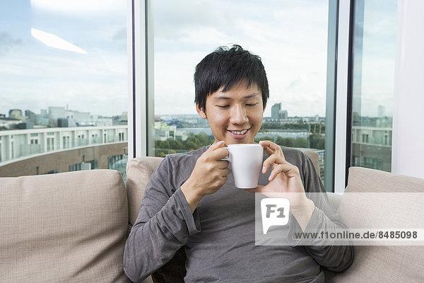 Mann Tasse halten Mittelpunkt Kaffee Interior zu Hause Erwachsener zu Hause