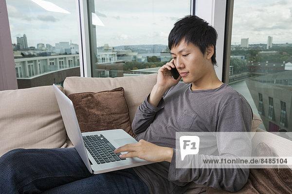 benutzen  Mann  Notebook  Zimmer  Mittelpunkt  Gespräch  Gespräche  Unterhaltung  Unterhaltungen  Wohnzimmer  Erwachsener