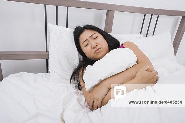 liegend  liegen  liegt  liegendes  liegender  liegende  daliegen  Frau  Kopfschmerz  Bett  jung  Schmerz