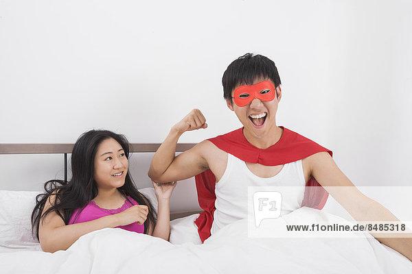 Portrait  Frau  Mann  Begeisterung  Superheld  Bett  Kostüm - Faschingskostüm