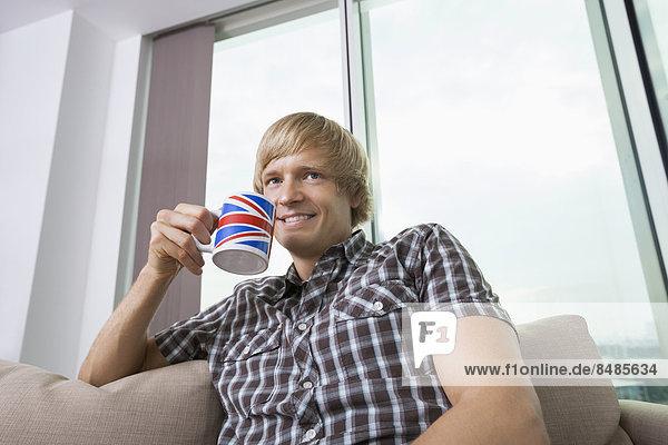 Interior  zu Hause  Mann  Tasse  lächeln  Zimmer  Erwachsener Mittleren Alters  Erwachsene Mittleren Alters  Kaffee  Nachdenklichkeit  Wohnzimmer