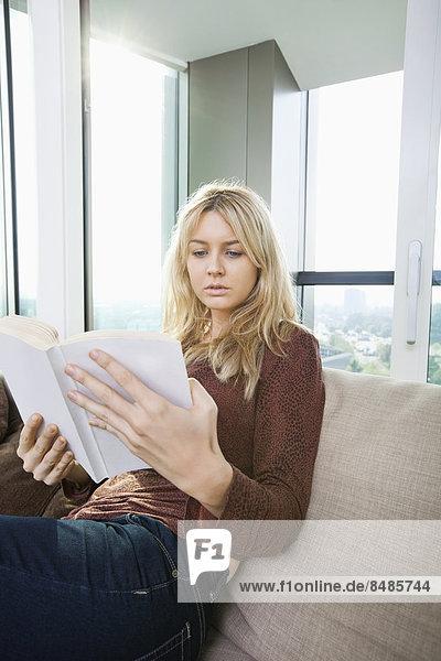 Interior  zu Hause  Frau  Entspannung  Buch  Zimmer  jung  Taschenbuch  Wohnzimmer  vorlesen