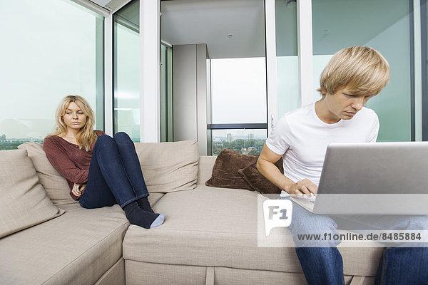 Interior  zu Hause  nebeneinander  neben  Seite an Seite  benutzen  Frau  Mann  Notebook  Zimmer  Depression  Wohnzimmer