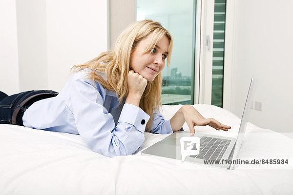 liegend  liegen  liegt  liegendes  liegender  liegende  daliegen  benutzen  Geschäftsfrau  Notebook  Bett  jung