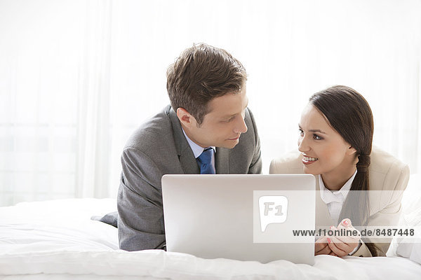 Business couple with laptop looking at each other in hotel room
