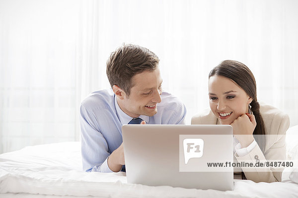 Young business couple using laptop in hotel room