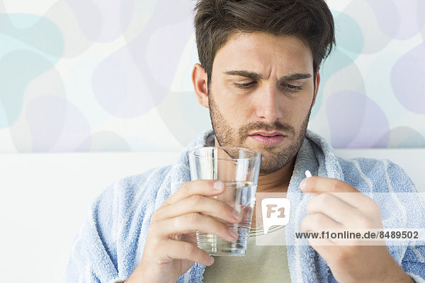 Sick man taking medicine in bedroom at home