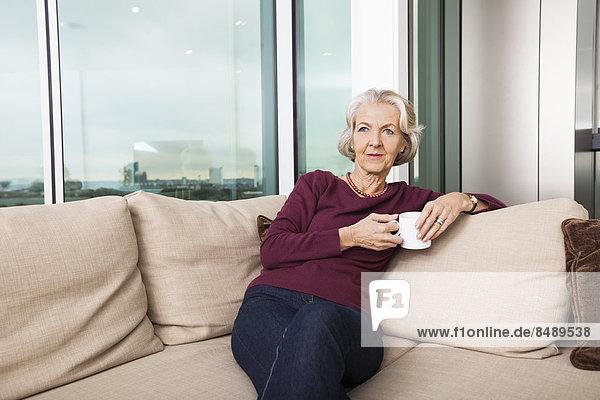 sitzend  Interior  zu Hause  Senior  Senioren  Frau  Couch  Becher  Kaffee