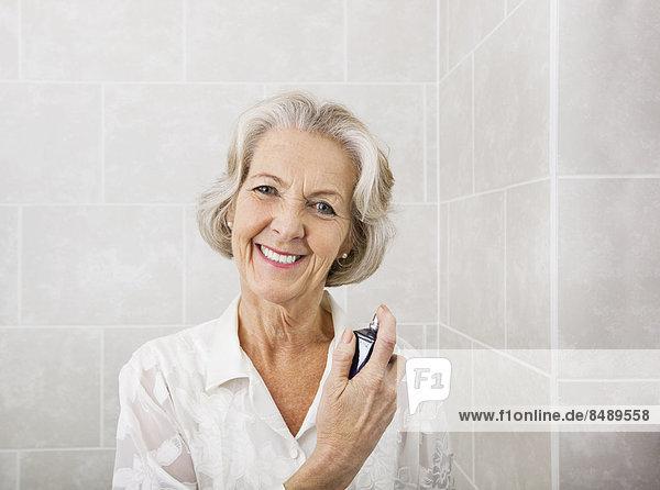 Senior Senioren Portrait Frau Fröhlichkeit Badezimmer besprühen Parfüm