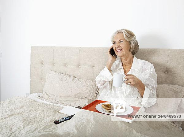 Senior  Senioren  Frau  antworten  Fröhlichkeit  Telefon  Bett  Handy  Frühstück