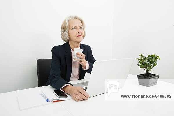 Senior  Senioren  Geschäftsfrau  Schreibtisch  Büro  Kaffee  Nachdenklichkeit