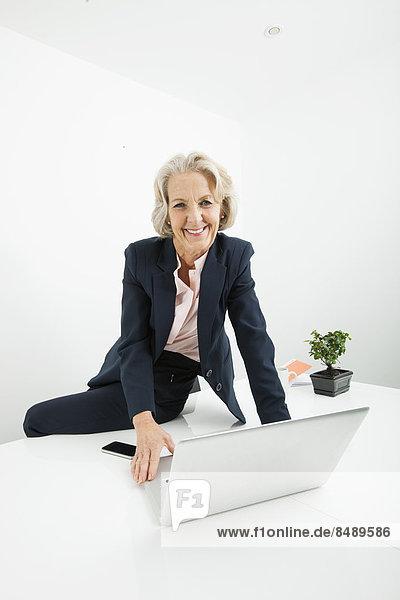sitzend  Senior  Senioren  Portrait  Geschäftsfrau  Schreibtisch  Notebook  Büro