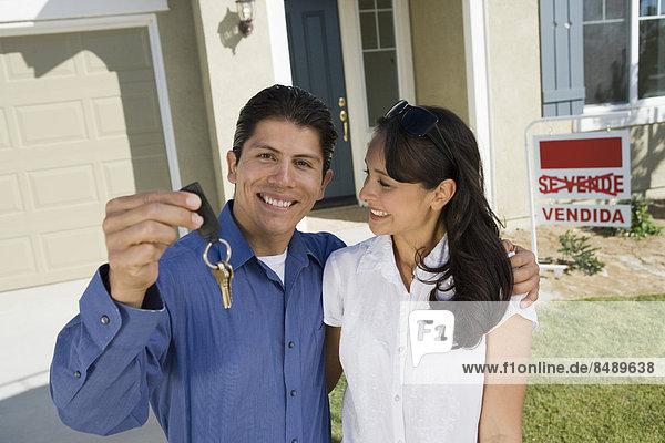 Außenaufnahme Portrait halten jung Schlüssel Eigentumswohnung neues Zuhause