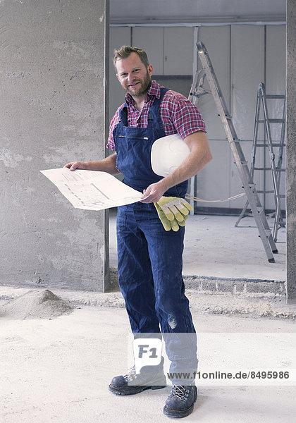 Handwerker auf Baustelle mit Bauplan
