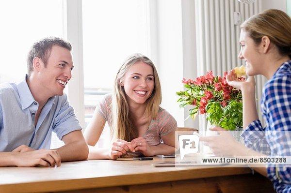 Drei junge Leute sitzen an einem Tisch und reden und lächeln.