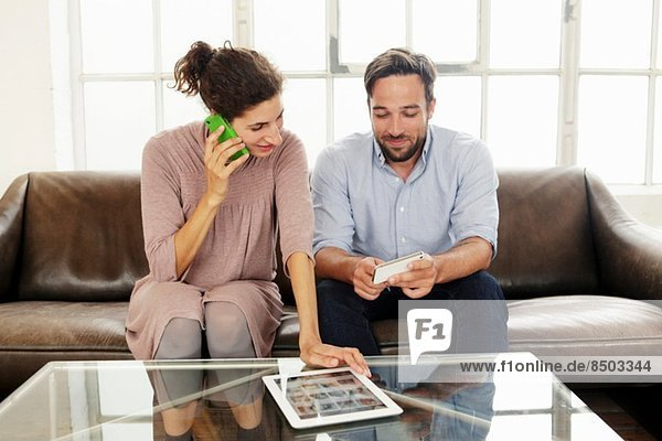 Mittleres erwachsenes Paar mit digitalem Tablett  Frau am Handy