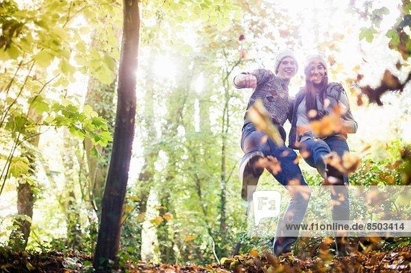 Junges Paar spielt mit Herbstblättern im Wald