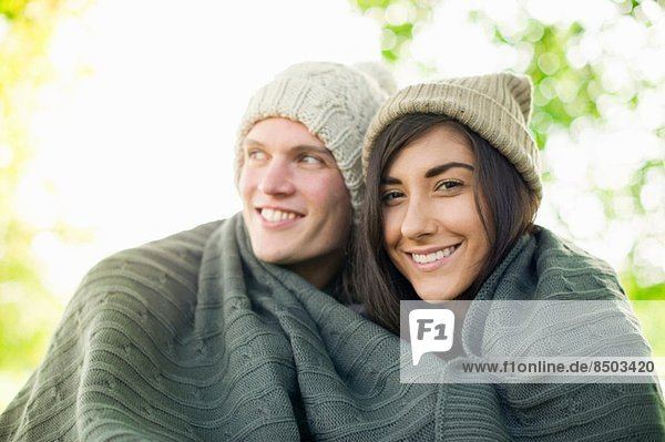 Young couple wearing knit hats wrapped in blanket