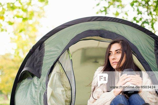 Junge Frau im Zelt mit Flasche