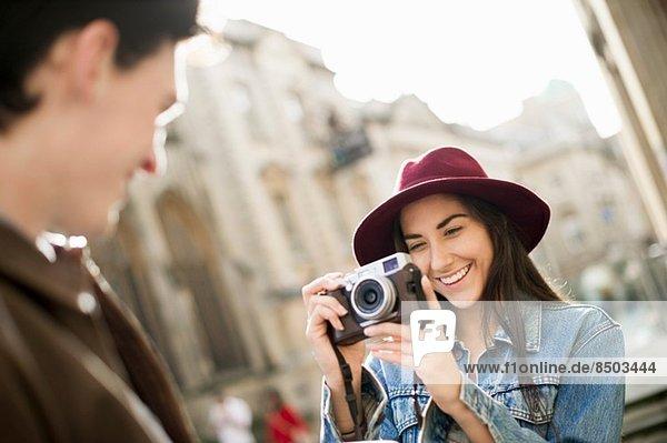 Junge Frau fotografiert Mann