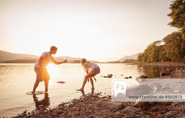 Junges Paar beim Paddeln im See  Cumbria  England  UK