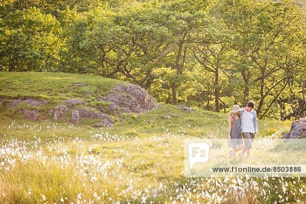 Couple walking in field  Cumbria  England  UK