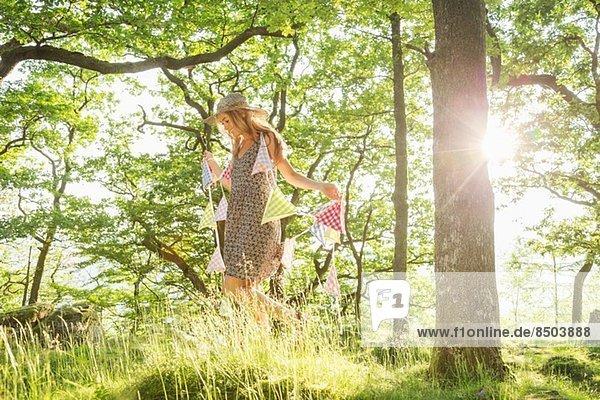 Junge Frau beim Spaziergang mit der Fahne im Wald
