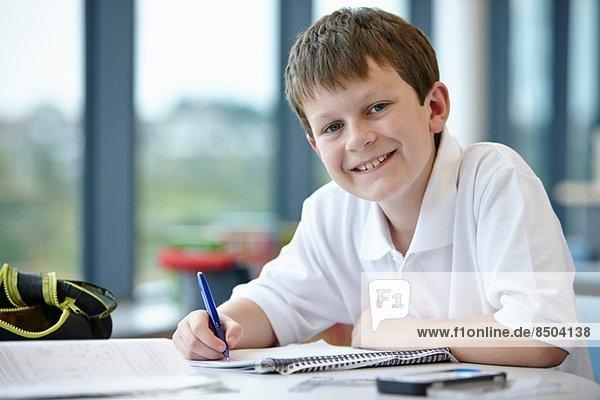 Porträt eines Schülers beim Schreiben im Unterricht