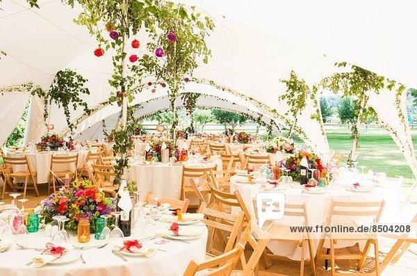 Dekorierte Tische im Gartenzelt bei der Hochzeitsfeier