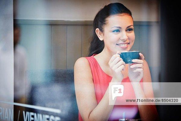 Junge Frau sitzend im Café mit heißem Getränk