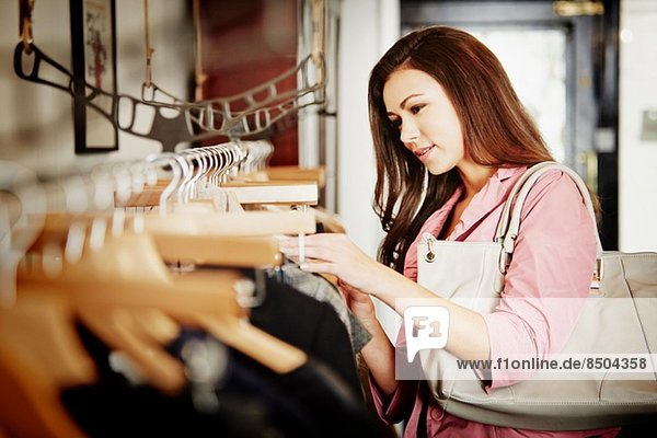 Young woman looking at selection of clothes on clothes rail