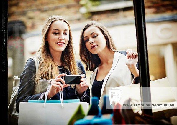 Junge Frauen beim Schaufensterbummel,  Fotografieren mit dem Smartphone