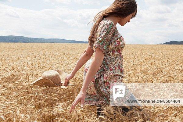 Mittlere erwachsene Frau  die durch das Weizenfeld läuft. Mittlere erwachsene Frau, die durch das Weizenfeld läuft.