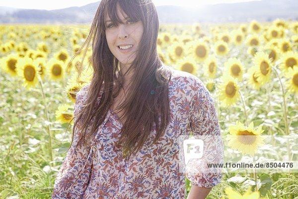 Mittlere erwachsene Frau im Feld der Sonnenblumen