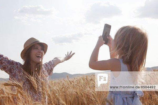 Mädchen fotografiert Mutter im Weizenfeld mit offenen Armen Mädchen fotografiert Mutter im Weizenfeld mit offenen Armen