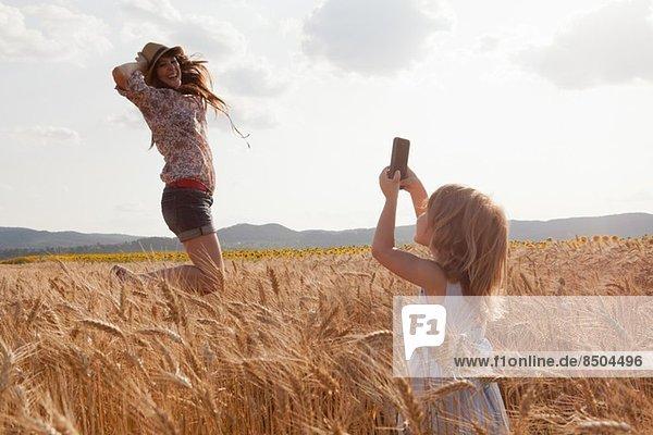 Mädchen fotografiert Mutter im Weizenfeldspringen Mädchen fotografiert Mutter im Weizenfeldspringen