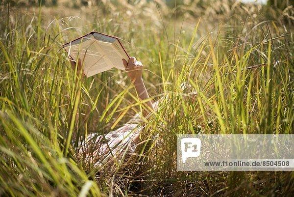 Frau in langem Gras liegend Lesebuch